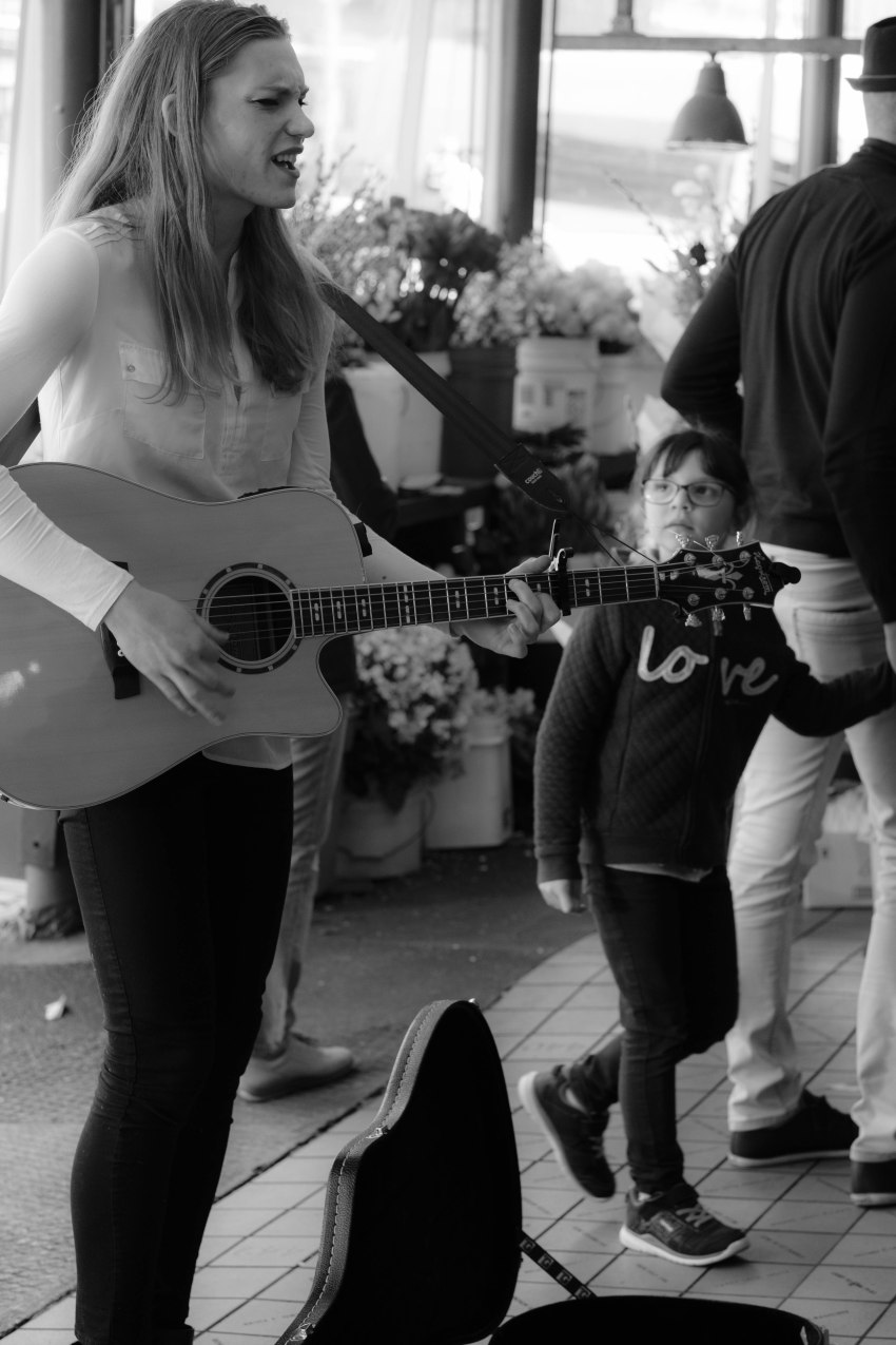 Claire Michelle busking young girl looks on